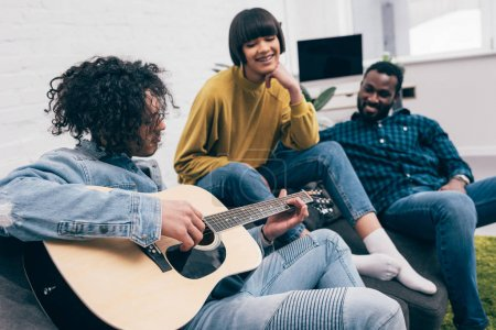 side view of mixed race young man playing guitar to multicultural friends