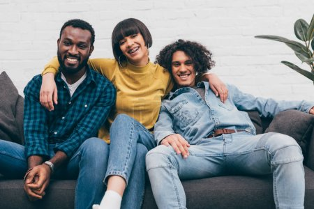 mixed race woman embracing two smiling male friends on couch