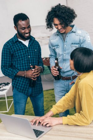 young woman showing laptop screen to multiethnic male friends
