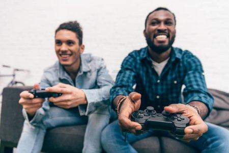 Foto de Amigos varones multiétnicas con joysticks video juego - Imagen libre de derechos
