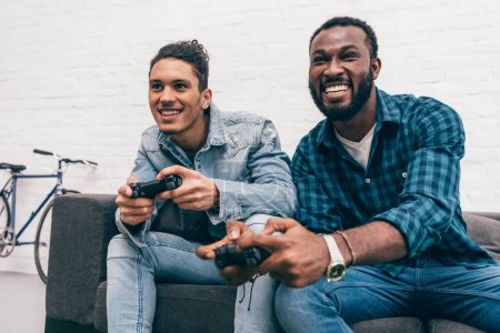 smiling multicultural young male friends with joysticks playing video game