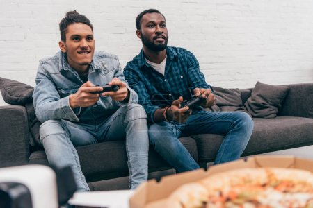 Photo for Multicultural young male friends with joysticks playing video game - Royalty Free Image