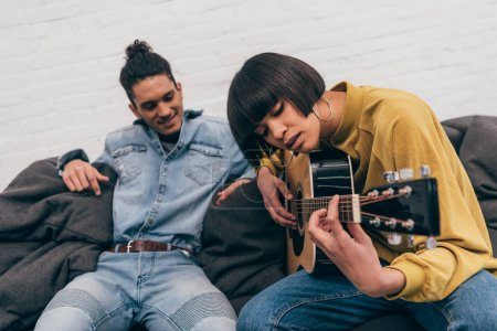 young mixed race woman playing on acoustic guitar to boyfriend
