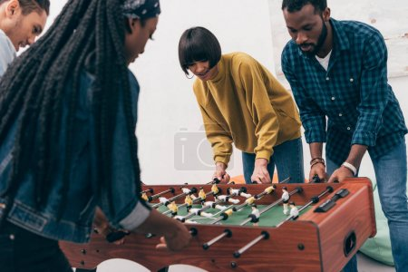 young multiethnic friends playing table soccer