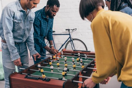 side view of multiethnic friends playing table football