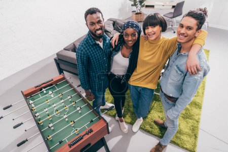 high angle view of multicultural friends standing near table football board