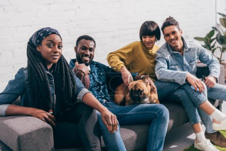 group of young multiethnic friends sitting on couch with dog