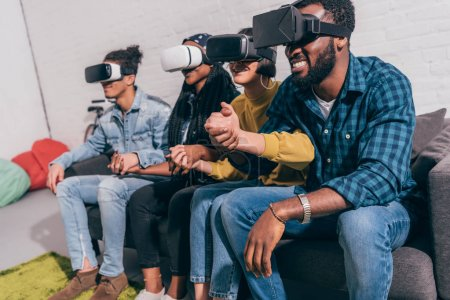 young multicultural friends using virtual reality headsets and holding hands of each other