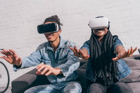 young smiling friends sitting on couch and using virtual reality headsets