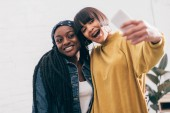 smiling young multicultural female friends taking selfie