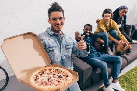 Photo pour Vue d'angle élevé d'homme jeune de race mixte tenant la boîte à pizza et faisant le geste de paix et amis assis derrière le canapé avec le bouledogue français - image libre de droit