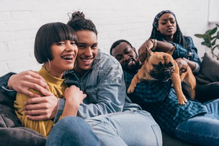 young smiling group of multicultural friends sitting on couch with dog