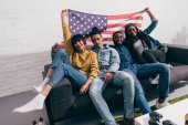 group of young multicultural friends sitting on couch with flag of USA