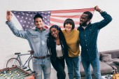 young multiethnic friends with flag of USA standing near table football board