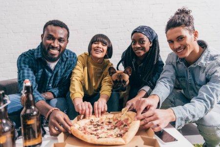 group of smiling young multiethnic friends with french bulldog taking pizza