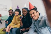 young mixed race doing selfie with multiethnic friends in party hats
