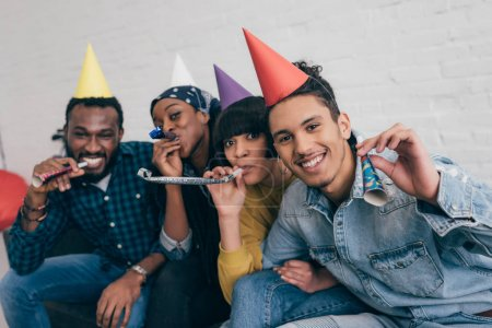 young multiethnic friends in party hats celebrating with party horns