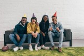 smiling group of young multiethnic friends in party hats sitting on couch