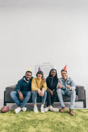 group of smiling young multiethnic friends in party hats sitting on couch