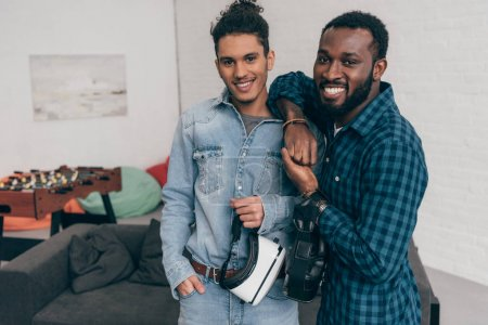 two smiling multicultural young male friends standing with virtual reality headsets