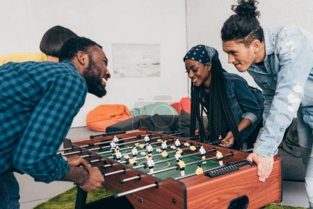 multicultural young friends playing table football