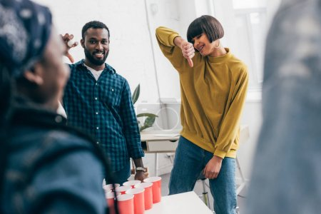 friends playing beer pong and young woman doing thumb down