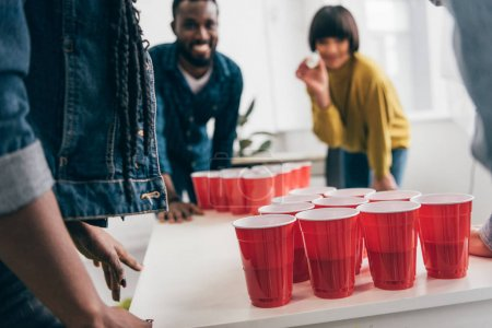 cropped shot of multicultural group of friends playing beer pong at table