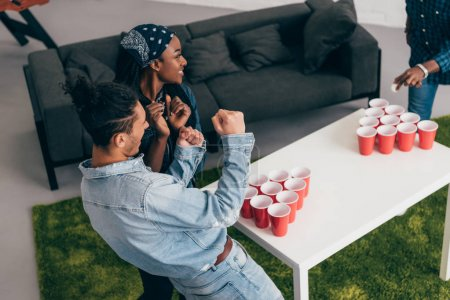 cropped shot of multicultural group of friends playing beer pong at table and young man doing winner gesture