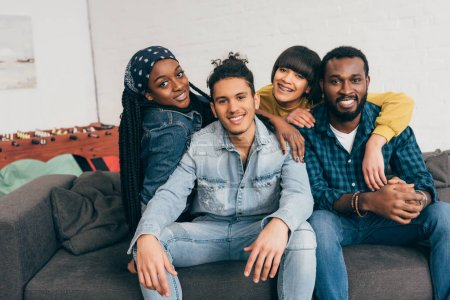 smiling group of young multiethnic friends embracing each other on couch