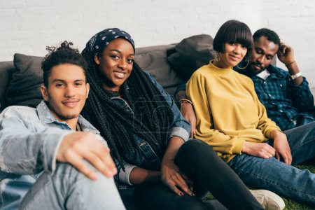 smiling group of young multiethnic friends sitting on floor near couch