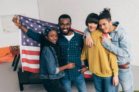 four multiethnic friends standing with flag of USA