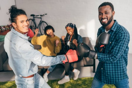 smiling multicultural male friends doing sparring in boxing gloves and two women cheering up them