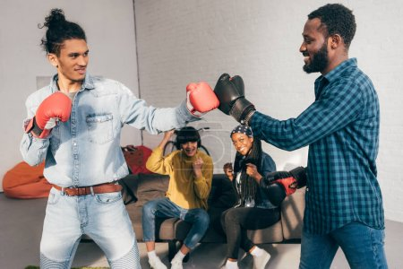 multicultural male friends doing sparring in boxing gloves and two women cheering up them