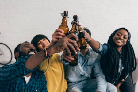 smiling multicultural friends clinking bottles of beer