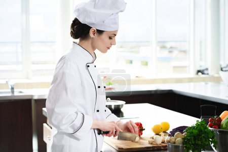 Professional female chef cutting ingredients for dish