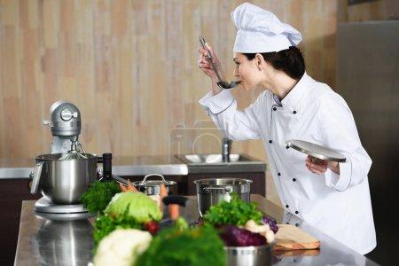 Female chef tasting dish on restaurant kitchen