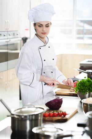 Professional female cook in uniform cutting ingredients on kitchen table