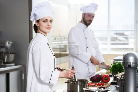 Professional chefs working by stove on modern kitchen