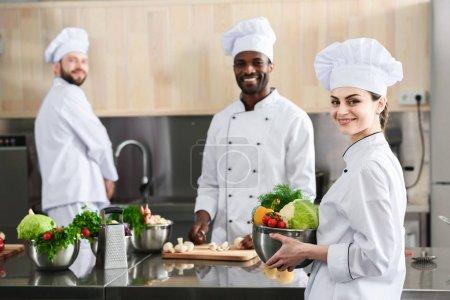 Multiracial chefs team working on professional restaurant kitchen