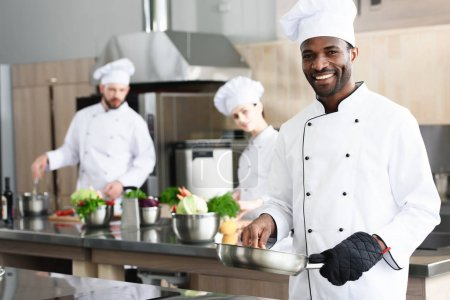African american chef cooking by his multiracial colleagues