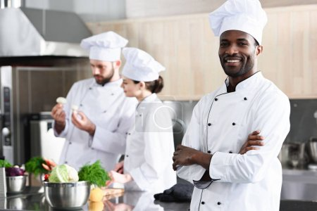 African american chef standing with folded arms in front of his colleagues on kitchen