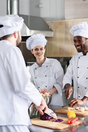 Multiracial chefs team smiling and cooking on modern kitchen