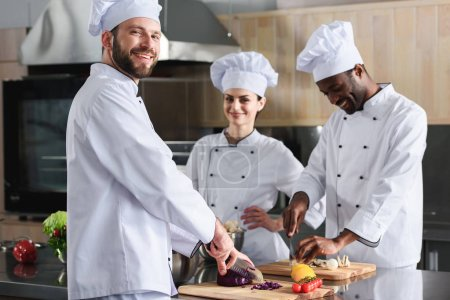 Multiracial team of cooks smiling while cutting ingredients by kitchen table