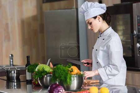 Professional female chef cutting ingredients on kitchen table