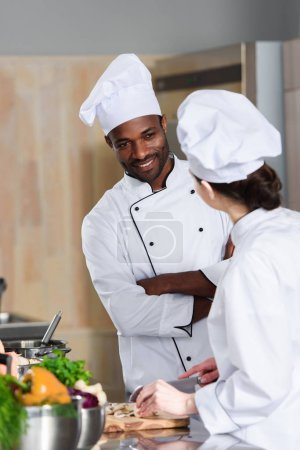 Multiracial team of cooks talking while cooking on modern kitchen