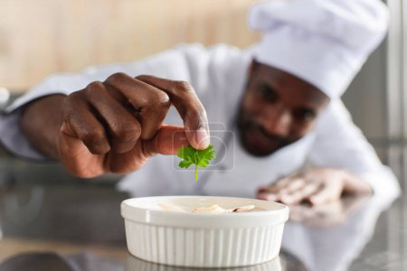 Close-up view of african american chef garnishing dish on restaurant kitchen