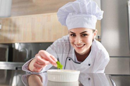 Female chef garnishing dish on restaurant kitchen