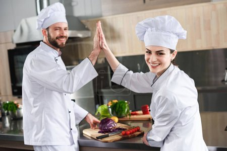 Professional chefs giving high five on modern kitchen