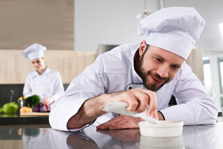 Male chef garnishing dish on restaurant kitchen in front of female cook