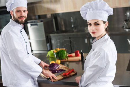 Professional chefs looking at camera by table with cooking ingredients
